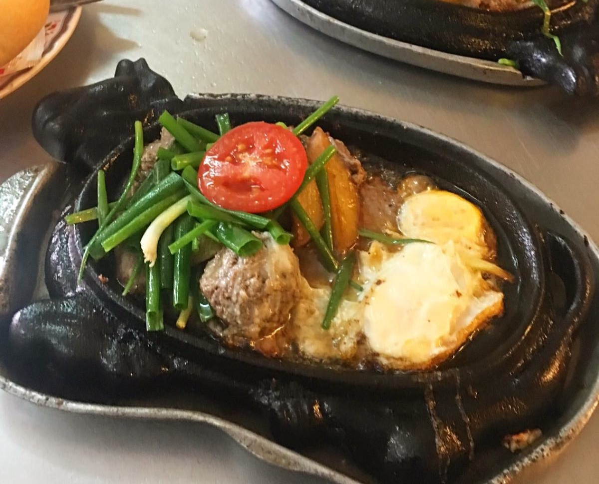 Bò bít tết - beef steak is commonly served on cow-shaped cast iron pans